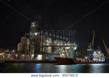 Cargo Crane, Ship And Grain Dryer In Port. At Night