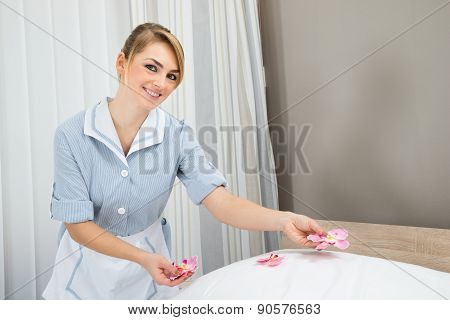Housekeeper Decorating Bed With Petals