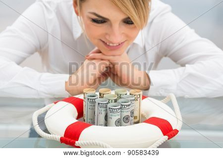 Businesswoman With Lifebuoy Protecting Banknote