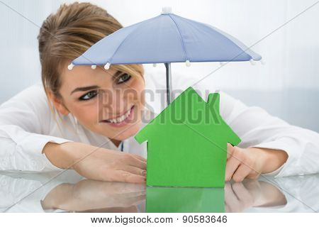 Businesswoman With House And Umbrella