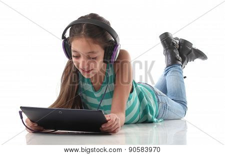 Beautiful pre-teen girl on the floor usin a tablet computer