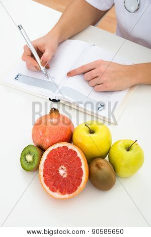 Dietician Writing Prescription With Fruits On Desk