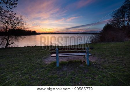 Colorful Sunset Over Lake Shore With Bench