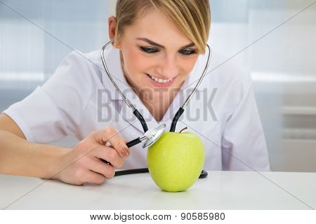 Female Dietician Examining Green Apple
