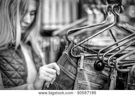 Beautiful blonde female looking jeans in the boutique
