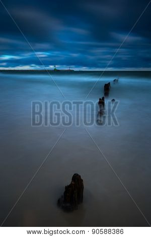 Baltic sea shore with old wooden breakwater palisade