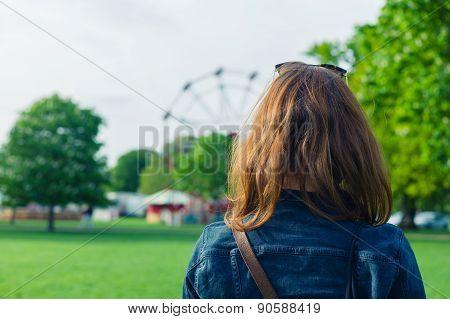 Woman In Park Looking At Fun Fair