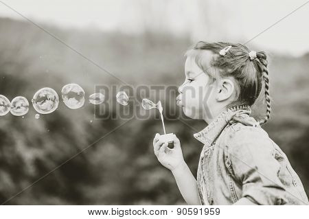 Happy Little Pretty Girl Outdoor In The Park Blowing Bubbles