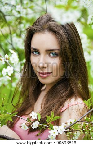 Close up portrait of a beautiful young brunette woman on the background of the cherry blossoms, spring park