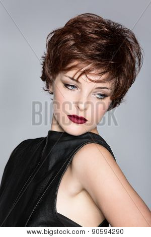 beautiful young woman with red hair wearing short pixie crop hairstyle on studio background
