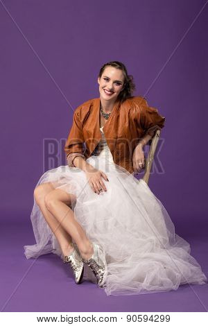 portrait of modern bride with tulle wedding dress wearing sequin shoes and leather jacket sitting against a purple background with retro effect