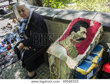 TBILISI, GEORGIA - MAY 01, 2015: An elderly woman sells portrait of Joseph Stalin on Dry Bridge market in Tbilisi, Georgia. Dry bridge today is most famous flea market in Georgia.