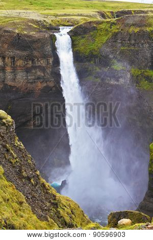 Spectacular waterfall Hayfoss in Iceland. Vertical cliff, from which the powerful waterfall flies on black stones