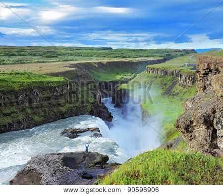 Delighted woman tourist on the shore of the huge waterfall Gyullfoss. Summer in Iceland