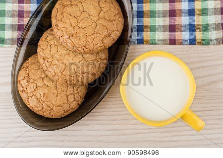 Round Cookies In Black Dish And Cup Of Milk On Table
