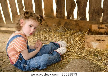 Child Sits Ondirty Floor In Hen Coop.