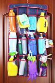 pic of household  - Household chemicals in holder hanging on wooden door background - JPG