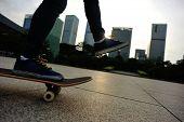 pic of skateboarding  - woman skateboarder legs riding on skateboard at sunrise city - JPG