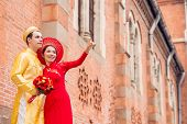 image of national costume  - Beautiful bride in Vietnamese national costume showing something to her husband - JPG