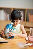 stock photo of schoolgirl  - Asian schoolgirl looking through microscope at class - JPG