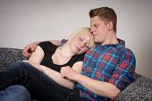 picture of cuddle  - young couple cuddling and relaxing on sofa - JPG