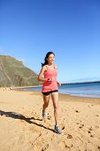 picture of biracial  - Runner sports athlete running woman on beach sweating and jogging - JPG
