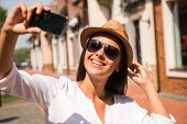 stock photo of funky  - Beautiful young funky woman adjusting her hat and making selfie while standing outdoors - JPG