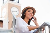 picture of funky  - Low angle view of beautiful young woman in funky hat looking away and smiling while standing outdoors - JPG