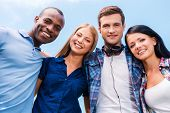 stock photo of bonding  - Low angle view of four happy young people bonding and looking at camera with smile with blue sky in the background - JPG