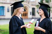 picture of graduation gown  - Two happy young women in graduation gowns holding diplomas and talking - JPG