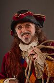 image of vicious  - Portrait of smiling old redhead pirate holding rope studio shot - JPG