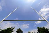 stock photo of spotlight  - Rugby goal posts with stadium spotlights and blue sky on the background - JPG