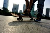 pic of skate board  - young woman skateboarder tying shoelace at skate park - JPG