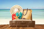 foto of mole  - Travel concept with old suitcase on wooden planks full of beach accessories - JPG