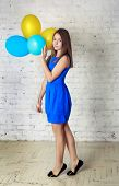 pic of toe  - Beautiful teen girl in blue dress with long hair holding colorful baloons standing on the tips of toes in front of white brick wall