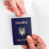 stock photo of passport cover  - an image of Ukrainian passport in hand on a white background