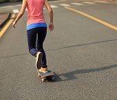 stock photo of skateboard  - one young woman skateboarder skateboarding on road - JPG