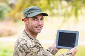 picture of soldier  - Soldier looking at tablet pc in park on a sunny day - JPG