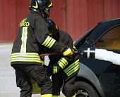 image of firehouse  - two firefighters in action with foam to put out the fire of the car - JPG