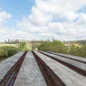 stock photo of old bridge  - old bridge with rusty metal rails near sea port - JPG