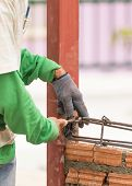 stock photo of concrete pouring  - Workers using steel wire and pincers rebar before concrete is poured on brick wall - JPG
