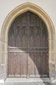 picture of stud  - Medieval decorative wooden studded arched double door with ancient stone surround