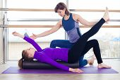 stock photo of pilates  - Aerobics Pilates personal trainer helping women group in a gym class - JPG