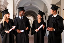 stock photo of graduation gown  - Four college graduates in graduation gowns walking along university corridor and talking - JPG