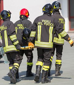foto of firefighter  - Four brave Firefighters carry a fellow firefighter with the medical stretcher - JPG