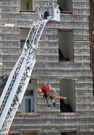 picture of firemen  - fearless fireman during an exercise carries the stretcher with the climbing rope - JPG