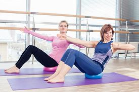 stock photo of senior class  - Aerobics Pilates personal trainer helping women group in a gym class - JPG