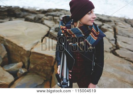 Female tourist wrapped up in warm scarf enjoying amazing nature on a cliff