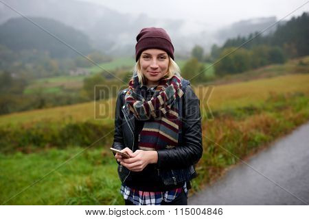Woman wanderer using cell telephone while hiking in mountains in cold day during autumn weekend