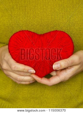 Closeup On Red Heart Made From Wool In Hand Of Woman